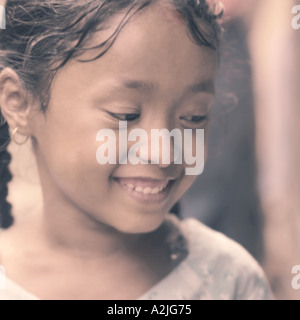 Young Nepalese girl smiling and looking away from camera. - Stock Photo