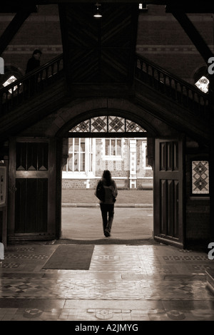 Young woman walking through passageway with lone figure overhead - Stockfoto