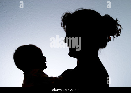 Silhouette of mother holding baby daughter - Stock Photo