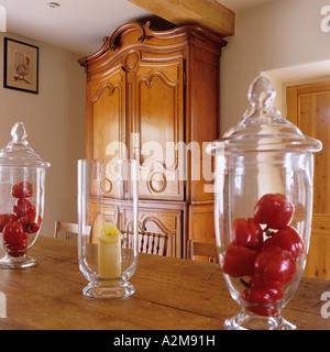 Table decoration of red peppers in glass bell jars with antique wardrobe in background - Stock Photo