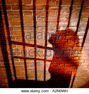 Shadow on a brick wall of a woman behind bars, shown in profile, hands tied behind her back. - Stock Photo