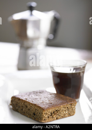 coffe cake slice on side plate with coffe maker and a shot of expresso in the background blurred - Stock Photo
