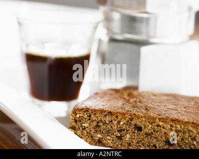 coffe cake slice on side plate with coffee maker and a shot of expresso in the background blurred - Stock Photo