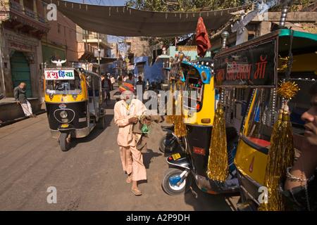 India Rajasthan Jodhpur old city man walking past decorated auto rickshaws - Stockfoto