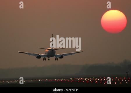 passenger airplane landing on airport Munich at sunset, Germany, Bavaria, Munich - Stock Photo