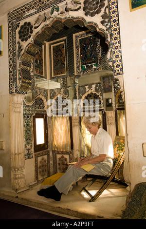 India Rajasthan Jodhpur old city Singhvis Haveli older western woman sitting in shisha room - Stockfoto