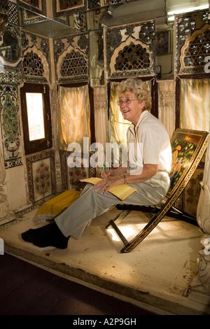 India Rajasthan Jodhpur old city Singhvis Haveli older western woman sitting in bed and breakfast shisha room - Stockfoto