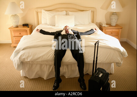 A businessman lying on a bed - Stock Photo