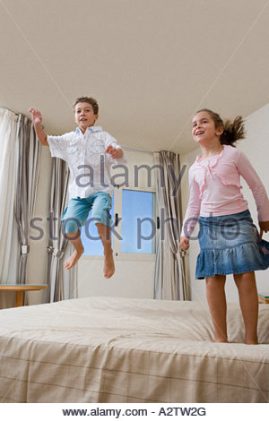 Children jumping on bed - Stock Photo