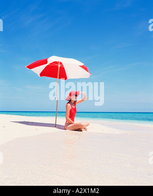 Young woman in red swimsuit sitting under sun umbrella alone on a deserted beach. - Stockfoto