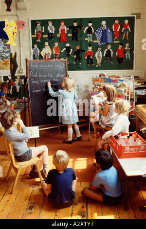 Group of young school children in classroom. Girl writing with chalk on blackboard during lesson. - Stock Photo