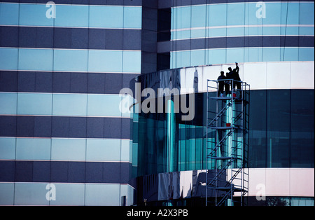 Two men on scaffolding outside modern commercial building. - Stock Photo