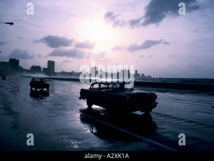 Driving along the seafront at sunset in old American cars, Havana, Cuba. The city is silhouetted and waves wash - Stock Photo