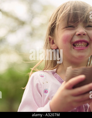 Young girl eating chocolate Easter egg and laughing - Stock Photo