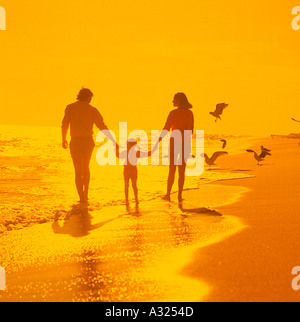 A mother father and daughter walking along the water's edge at the beach silhouetted against an orange sunset sky - Stock Photo