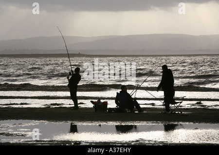 Sea fishermen struggle against the approaching tide on a sunny winter afternoon, Burnham-on-Sea, Somerset, UK. - Stockfoto