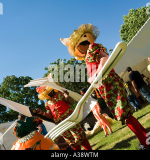 Two men  dressed up as exotic pigs carrying cutlery for a street carnival South Bank London England UK - Stock Photo