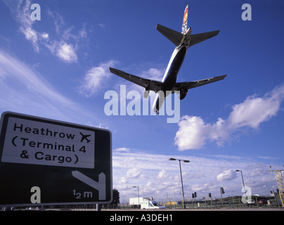 London Heathrow airport perimeter road with sign directing traffic to terminal 4 and cargo areas & plane descending - Stock Photo