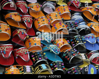 Colourful shoes for sale at a bazaar in Chandni Chowk in Delhi India - Stock Photo