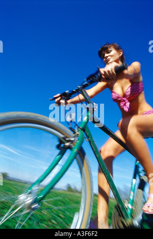girl on bicycle low angle wearing bikini - Stock Photo
