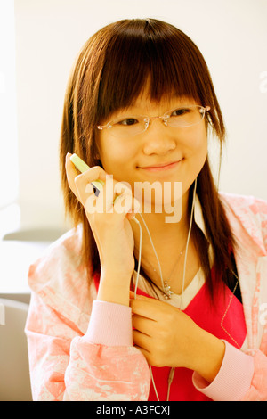 Close-up of a teenage girl listening to an MP3 player in the classroom - Stock Photo