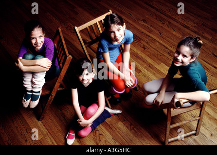 Four lovely young ladies pose for portraits in a practice room of their suburban dance studio sitting in chairs - Stock Photo