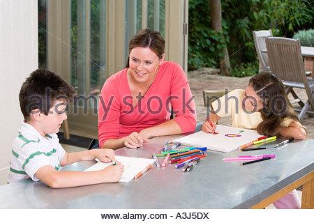 Mother watching children draw - Stockfoto