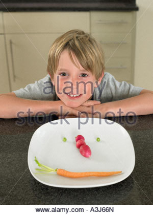 Boy with vegetable face on a plate - Stock Photo
