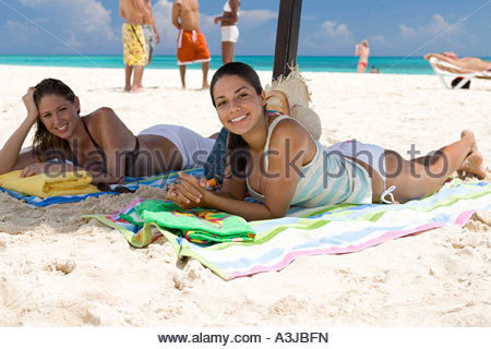 Two friends lying on beach - Stock Photo