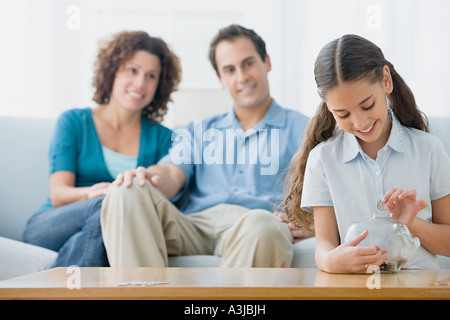 Girl putting coins in a piggy bank - Stock Photo