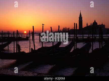 Venice San Giorgio Maggiore at dawn sunrise from the Molo Gondolas in foreground  Venice Veneto Italy - Stock Photo