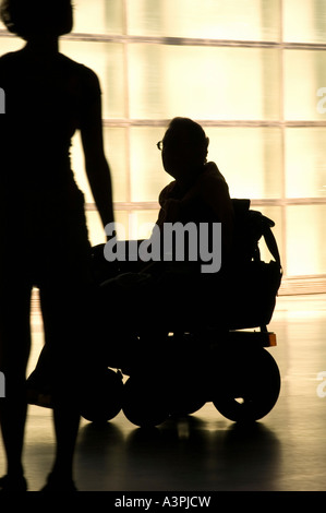 Silhouette of a man on a wheelchair looking at a young woman - Stock Photo
