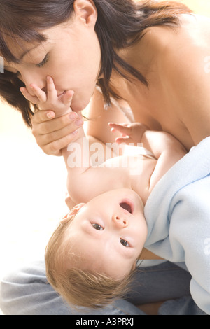 mother kissing baby's hand - Stockfoto