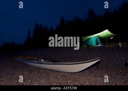 A sea kayak and a tent are illuminated at dusk in Lake Superior Provincial Park near Wawa Ontario Canada - Stock Photo