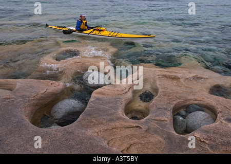 A sea kayakers at Grindstone Point in Lake Superior Provincial Park near Wawa Ontario Canada - Stock Photo