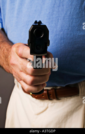 Man holding 9mm gun pointed at you - Stock Photo
