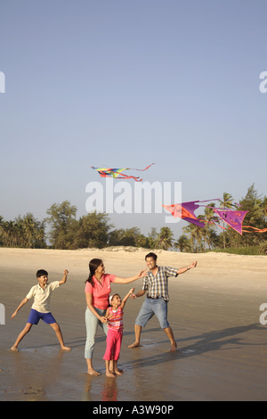 Mother and child on picnic flying a kite on beach enjoying sun sand and sea - Stock Photo