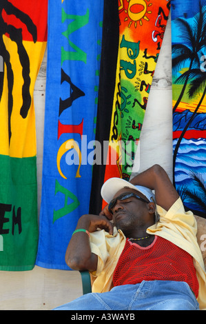 Man asleep shop selling towels and clothes Negril Jamaica - Stock Photo