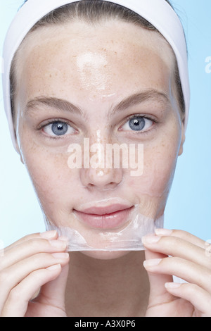 A young woman peeling off a face mask - Stock Photo