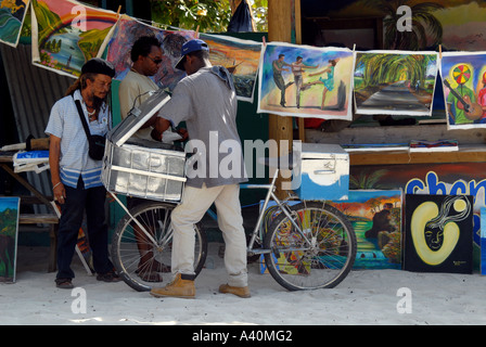 Paintings for sale and man selling coco bread Negril Jamaica - Stock Photo