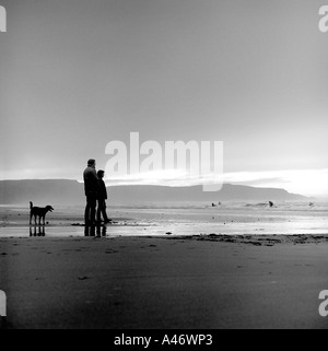 Romantic couple with their dog on Bude Beach Cornwall - Stock Photo