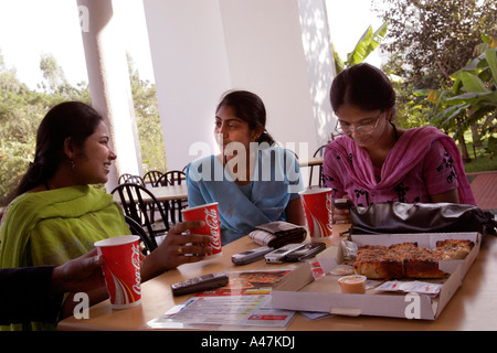 Young Indian women who works in the IT industry for Infosys eats western fast food during a lunch break in Bangalore - Stock Photo