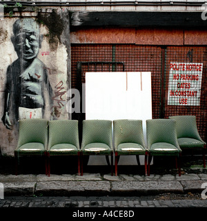 Used furniture dealers street display off Brick Lane in Londons East End with wall graffiti mural stencil possibly - Stock Photo