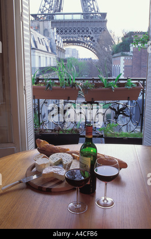 Bottle of wine on table with bread and cheese in apartment near Eiffel Tower - Stock Photo