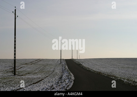 Rural road in landscape with snow on fields - Stock Photo