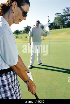 Mature couple playing golf - Stock Photo