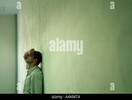 Man leaning against wall, holding head, long shot - Stock Photo