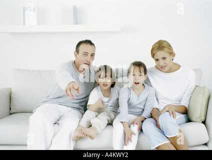 Parents with sitting on sofa with daughter and son, father pointing straight ahead - Stock Photo