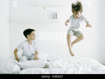 Boys on bed, one in mid air - Stock Photo