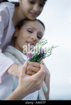 Girl embracing mother from behind, mother's hand over girl's, holding bouquet of wildflowers - Stock Photo